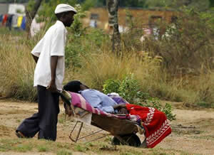 A man pushes his relative in a wheelbarrow to a Cholera Polyclinic, where victims of cholera are being treated in Harare, Zimbabwe. by AFP