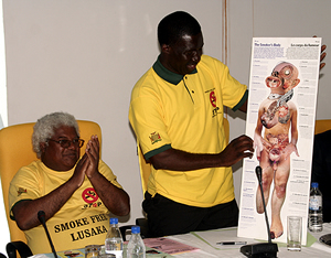 Dr. Fastone Goma of UNZA displays a placard on the effects of smoking during the launch of the smoke free Lusaka campaign while Dr. Lambert looks on.