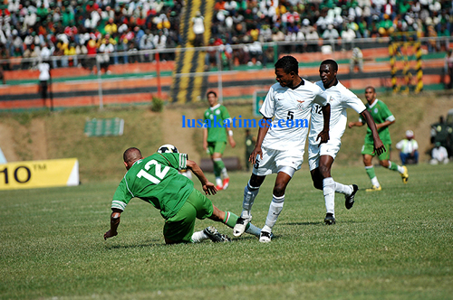 Algerian Djebbour tumbles down under pressure from Zambia's Nyambe Mulenga (c) and Francis Kasonde (r) during the 2010 FIFA world cup and nations cup qualifier at Konkola stadium in Chililabombwe
