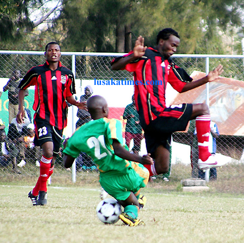 Zesco's Rodgers Kamwandi (c) tumbles with ball past Zanaco's Patrick Kabemba (r) during the KCM-FAZ rescheduled week 13 at Sunset stadium in Lusaka