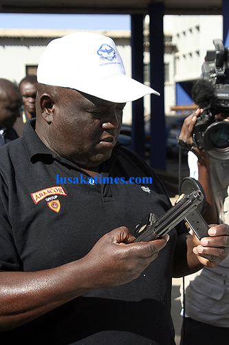 Lusaka district police commanding officer Greenwell Nguni examines a hand gun confiscated from criminals at the weekend