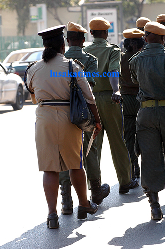 A police woman marching with a handbag strapped on her shoulder during the pubic serivce day commemoration in Lusaka