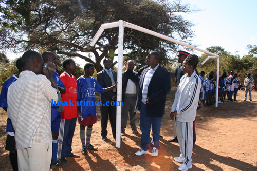 Chongwe district commissioner, Japhen Mwakalombe,handing over goal posts to the  Chinkuli community at Chinkuli sports field in Chongwe district while Lusaka province Sports co-ordinator,Doris Mulenga,looks on.