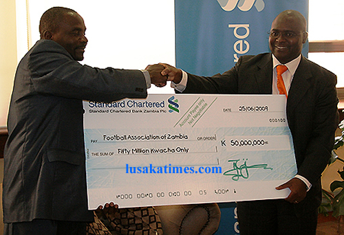 Sports minister Kenneth Chipungu (l) receives a dummy cheque of K50 Million from Standard Chartard Bank Regional head of Corperate affairs Luke Njobvu,a donation towards Zambia 2010 qualifier