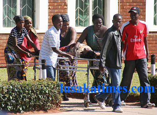 Family members take a sick relative to the casualty on a stretcher in the absence of health workers who are on strike at the University Teaching Hospital in Lusaka