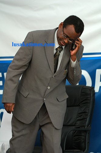 Vice president George Kunda walking out of the marquee to answer a call on a mobile phone