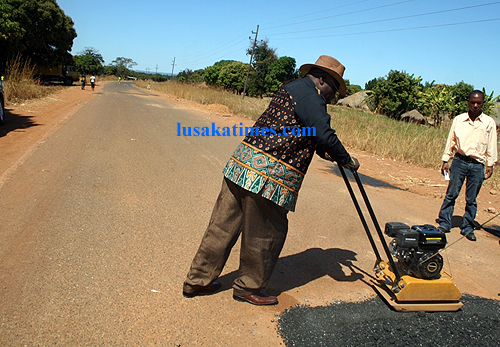 Luapula permanent secretary Jazzman Chikwakwa on the business end of a road repair machine on the Mansa Kashikishi road.