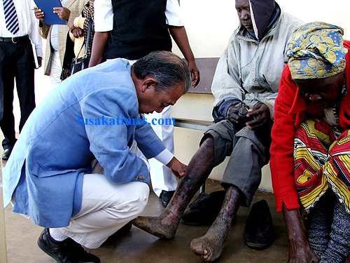 World Health Organization Goodwill Ambassador on Leprosy Yohei Sasakawa, examines sores on Robert Nangondo's feet, a leprosy patient at Liteta general hospital in Chibombo