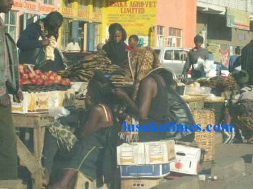 A vendor plaits hair while selling apples and fish