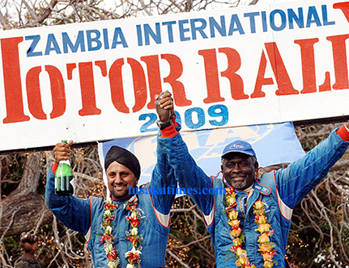 Muna Singh (l), his navigator Dave Sihoka raise hands  after popping champaigne upon winning the 2009 Zambia international motor rally