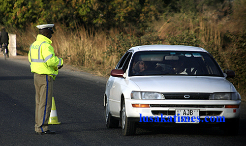 File:  A traffic policeman attending to a motorist at a roadblock near Chikankata in Mazabuka.