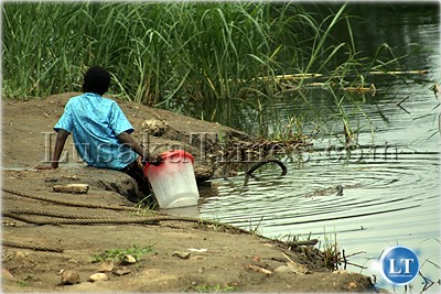 A young boy tries to draw water from the crocodile infested Kafue river because of lack of bore holes and other good sources of clean and adequate water.