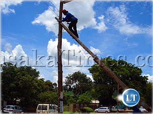 An unidentified female electrical engineer captured repairing high voltage power lines in Chipata