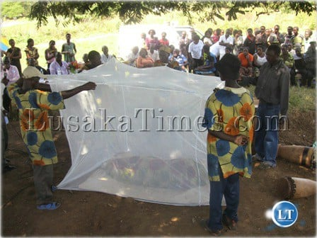 FILE: Community health workers demonstrating how a mosquito net is supposed to be spread when sleeping
