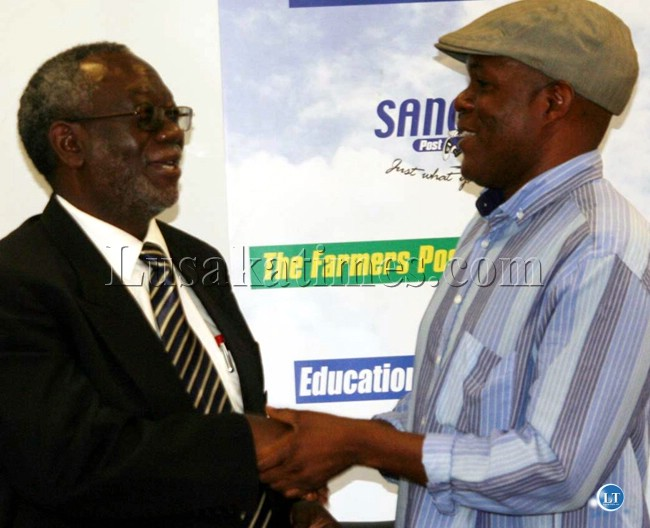 Information Minister Fackson Shamenda (l) and Post newspapers owner Fred Mmember clench hands after a meeting in Lusaka