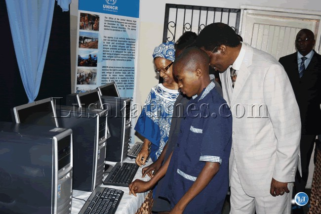 One of the boys at the Northmead Assembly of God Church-run Lazarus Community School tries out a new computer while  Bishop Joshua Banda and UNHCR rep Ms Joyce Mends-Cole look on
