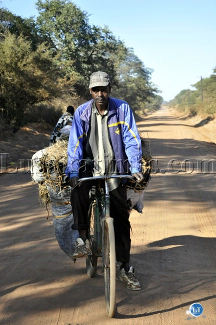 A man cycling  bags of charcoal for sale from Chongwe rural to Chelstone in Lusaka