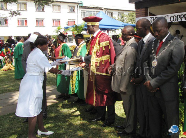 Copperbelt minister Davis Mwila hands over a certificate to one of the midwives at the graduation ceremony in Kitwe. Standing on his left is provincial medical officer Chandwa Ng'amba, district commissioner Elias Kamanga and Kitwe mayor Chileshe Bweupe