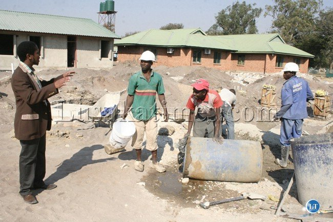 General Hospital acting Medical Officer Dr. David Kasongole talks to construction workers during the inspection of the Eye Hospital at Lewanika General Hospital in Mongu