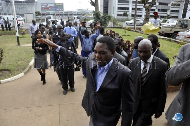 Hakainde Hichilema waves at party supporters as he walks into the Lusaka Central Police Station.