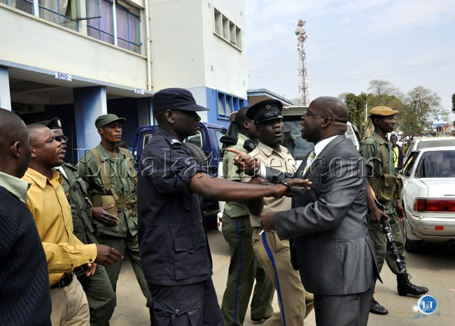 Police officers push Zambezi West Member of Parliament Charles Kakoma out of the Lusaka Central Police Station.