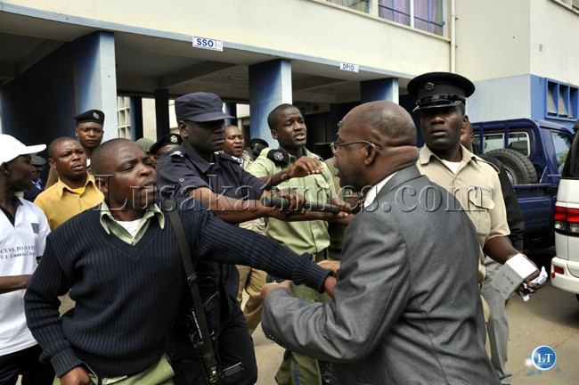 Police officers push Zambezi West Member of Parliament Charles Kakoma out of the Lusaka Central Police Station