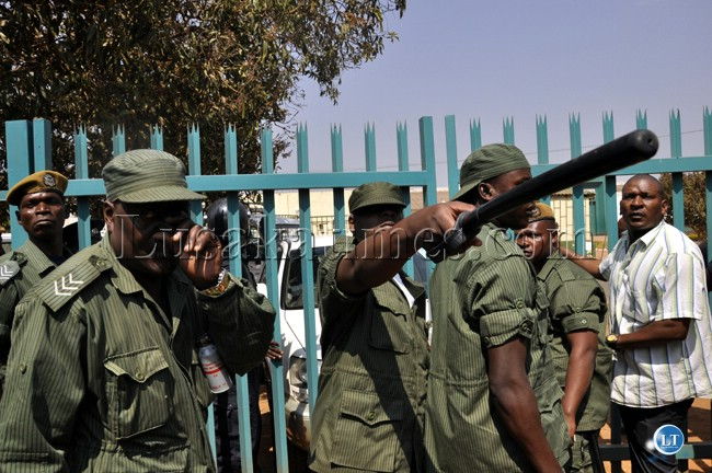 File : Police officers wield a short button against UPND cadres outside the Lusaka magistrate court