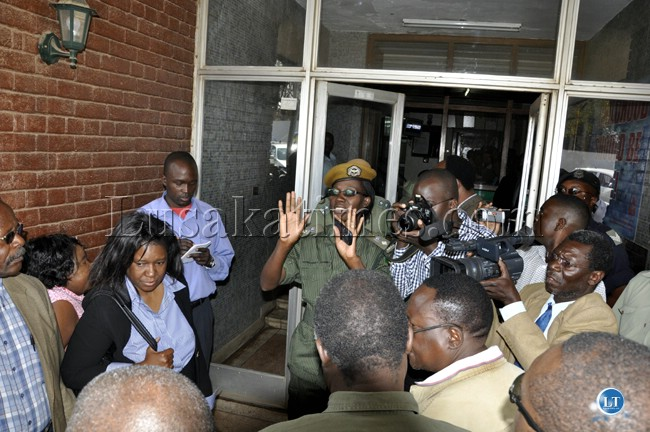 Zambia police spokesperson Charity Chanda restrains UPND officials from entering the police headquarters building