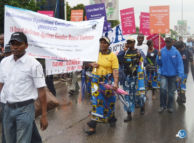 Women from various organisations carrying different placards denouncing Gender Based Violence during a march past to commemorate the 16 Days of Activism Against GBV in Lusaka