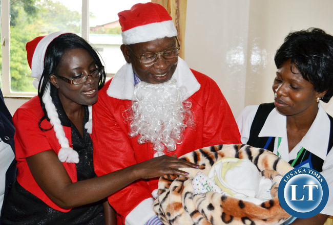 Health Minister Dr Joseph Kasonde (in Father Christmas fatigues) admires a Christmas baby when he visited the University Teaching Hospital maternity ward