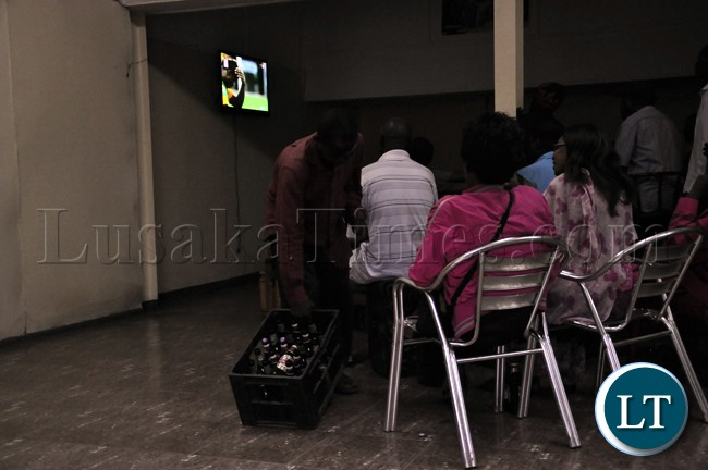 A bar attendant passes some drinks around during the televising of the Zambia Bukina Faso match at a certain Pub in Lusaka