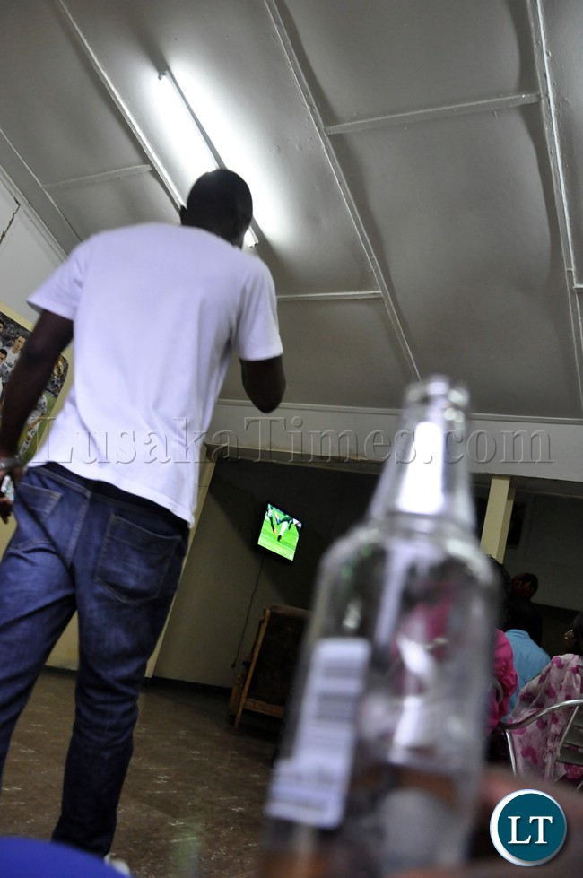 A man enters a pub where scores of soccer fans watched the Zambia Bukina Faso match in Lusaka