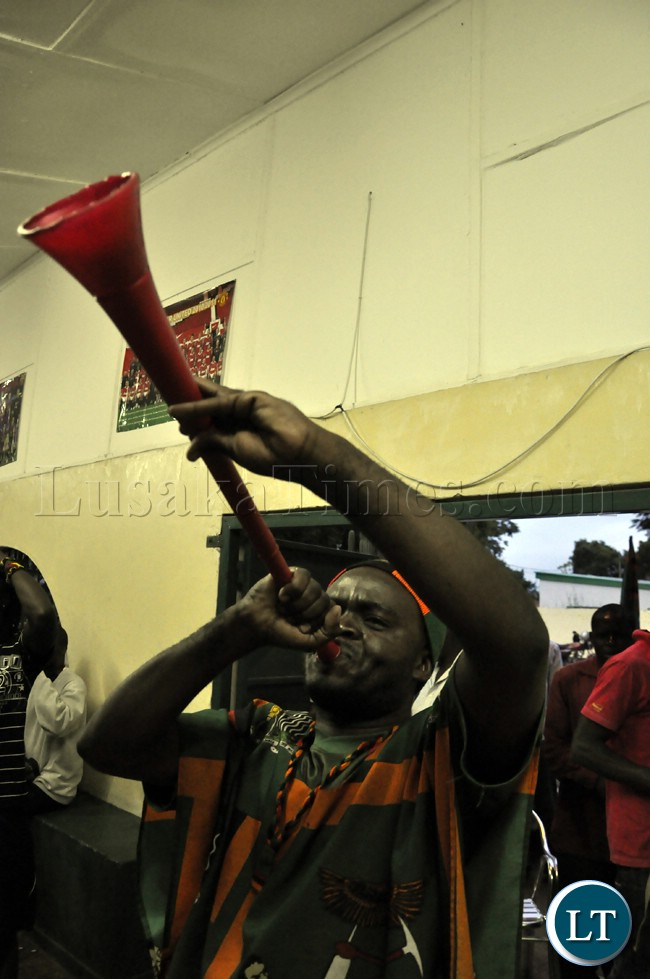 A soccer fans blows a vuvuzela (trumpet) during the Zambia Bukna Faso match.