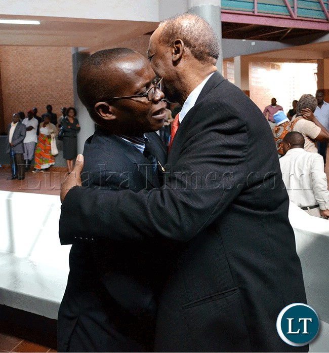 Former Information and Broadcasting Services Minister Ronnie Shikapwasha (right) and freelance journalist Chanda Chimba III hug at the Lusaka magistrate's court complex