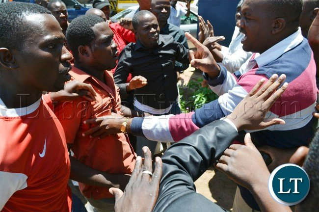 Police officers (right) try to control suspected riotous UPND cadres at Woodlands police station in Lusaka