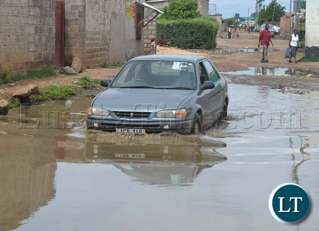 File:The heavy rainfall being experienced in some parts of the country have caused severe floods.  Here, a motorist wades in a flood of stagnate rainwater in Kanyama Township