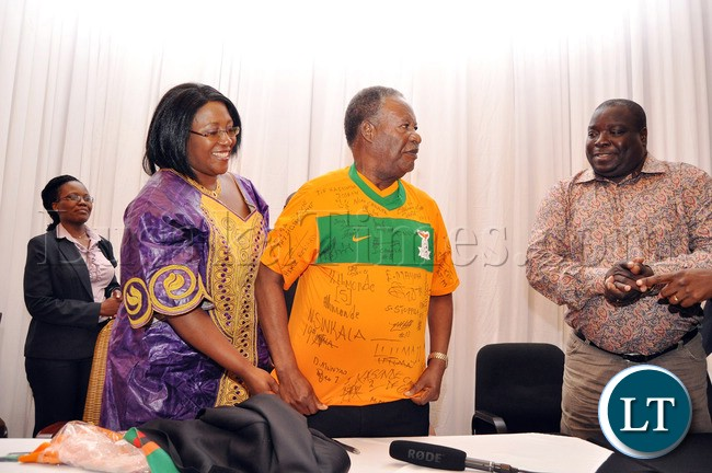 President Sata being helped to put on a Chipolopolo Jersey by First Lady Dr Christine Kaseba as Sports minister Chishimba Kambwili looks on