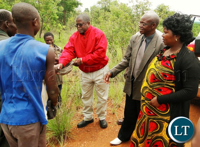 TRANSPORT, Works, Supply and Communication Minister Christopher Yaluma flanked by Mungwi DC Joyce Chanda (right) greets a team of locals who are engaged to crash stones for the construction of a 1 x 3 classroom block at Chileshemulkulu Primary school in his Malole Constituency in Mungwi district