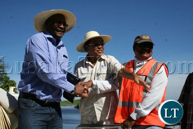 Western Province Permanent Secretary Emmanuel Mwamba shaking hands with Rankin Resident Engineer Ramesh Suryawanshi (r) while AVIC site Manager Liu Zhenjie showing directions during the visits of the bridges on Mongu