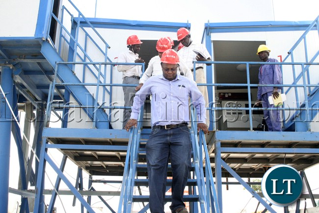 (Mongu-Kalabo Road) Western Province Permanent Secretary Emmanuel Mwamba coming out the stone mixing control room when he tour the AVIC bridge department at their comp site of Mongu–Kalabo Road
