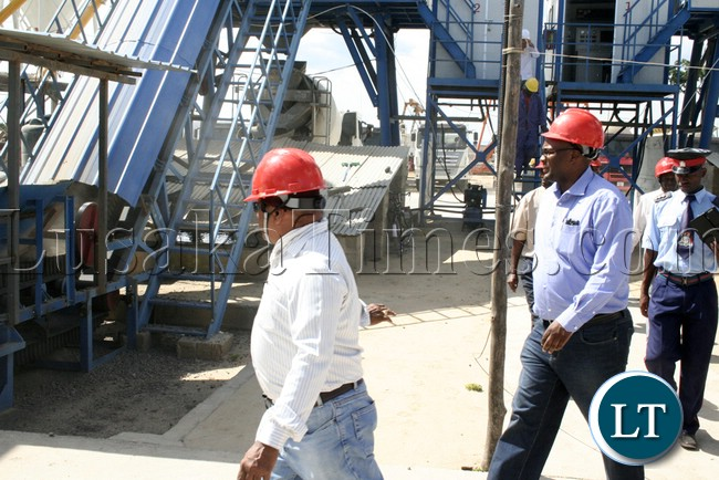 (Mongu-Kalabo Road) Western Province Permanent Secretary Emmanuel Mwamba being ushered the  way at the stone mixing  machine site when he tour the AVIC bridge department at their comp site of Mongu–Kalabo Road