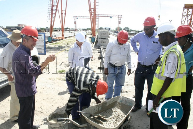 (Mongu-Kalabo Road) Western Province Permanent Secretary Emmanuel Mwamba third from (r) looking carefully how they mix the cement and stones during the tour of the AVIC bridge department at their comp site of Mongu–Kalabo