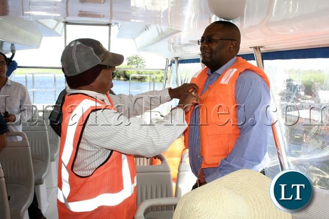 Rankin Resident Engineer Ramesh Suryawanshi helping to dress Western Province Permanent Secretary Emmanuel Mwamba  with the life jacket during the visits of the bridges on Mongu –Kalabo Road