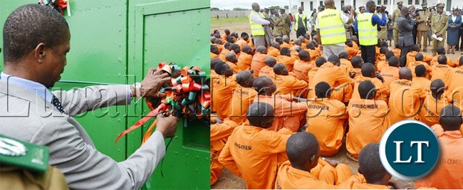 HOME Affairs Minister Edgar Lungu cuts a ribbon during commissioning of newly built Mwembeshi Maximum security prison in Mumbwa district .On the right, are some of the inmates waiting to be addressed by Mr Lungu