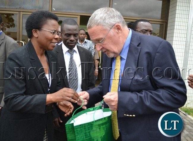 Vice President Dr Guy Scott receives a gift from Oxfam Zambia Director Nellie Nyang'wa at the New Government Complex in Lusaka yesterday during the official opening of the Oxfam conference on Preparing Zambia to Create the Future