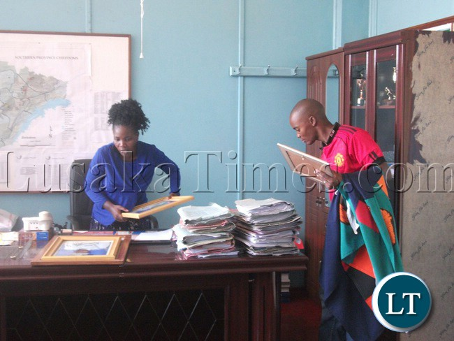 Southern Province Commissioner of Police Charity Katanga (left) captured being helped by her staff (right) to pack her belongings at her former office in Livingstone yesterday in readiness for ferrying of her luggage to the new provincial capital in Choma