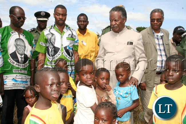 President Sata with little children , and to the far left is PF Candidate for Kapiri Eddie Musonda, Central Province Minister Phillp Kosamu and Commerce Minister Emmanuel Chenda in Ngambwe area during his campaign tour for the Kapiri by-elections in Kapiri, April 13, 2013.