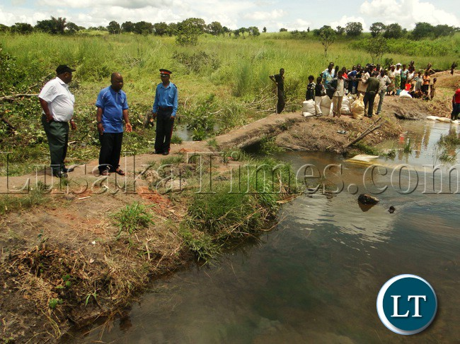 KASAMA District Commissioner (DC) (left) and Kasama May Francis Kombe in blue T/shirt at Chanda Mwamba Bridge during the inspection of Bridges in Kasama yesterday under full participation of community in the area