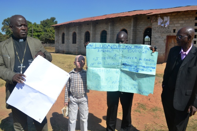 FATHER Richard Luonde with his Church Treasurer Burton Phiri holding showing poster and spokesperson Cuthbert Chuza after congregation members locked their church.