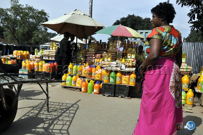 FILE: A street vendor who trades on juices waits for customers at her selling point in Livingstone